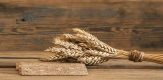 Sheaf of wheat as bread gifts of warm summer. Ears of wheat on old wooden table Stock Image