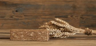 Sheaf of wheat as bread gifts of warm summer. Ears of wheat on old wooden table Stock Photos