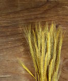 Sheaf of wheat ears. On the wooden background Royalty Free Stock Photos