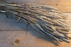 Sheaf of wheat. On the old wooden desk Royalty Free Stock Photos