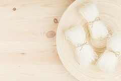 Sheafs raw asian cellophane noodles on plate on beige wooden board with copy space, top view. Stock Photos