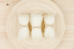 Sheafs raw asian cellophane noodles on plate on beige wooden board , top view. Stock Images