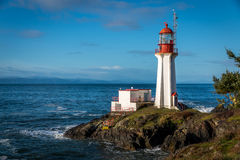 Shearingham Lighthouse. On Vancouver Island, British Columbia Canada as waves from the Pacific Ocean crash on its rocky shore Royalty Free Stock Photo