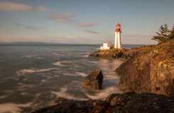 Shearingham Lighthouse. On Vancouver Island, British Columbia Canada as waves from the Pacific Ocean crash on its rocky shore Royalty Free Stock Photos