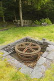 Sheave, horizontal recessed iron wheel. Stone lined pit with large iron wheel or sheave in it. Vivian Slate Quarry, Llanberis, Gwynnedd, Wales, United Kingdom Royalty Free Stock Photography