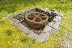 Sheave, horizontal recessed iron wheel. Stone lined pit with large iron wheel or sheave in it. Vivian Slate Quarry, Llanberis, Gwynnedd, Wales, United Kingdom Royalty Free Stock Images