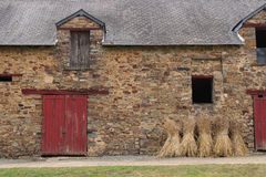 Sheaves of hay are put against the facade of a barn in Saint-Aubin-des-Chateaux (France) Royalty Free Stock Photos