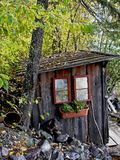 Shed. This picture was taken in NW Montana and shows an old lake shore shed with mirrors for windows and a flower box Royalty Free Stock Photo