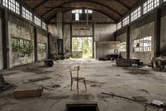 Shed in abandoned factory, central perspective. Perspective shed in abandoned factory, with empty chair in foreground Stock Image