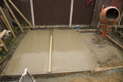 Shed base with poured Cement. Shed base construction with partially flatten cement and some recently poured with cement mixer in shot Royalty Free Stock Photo