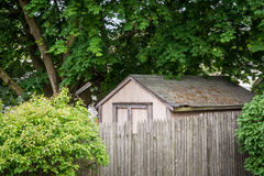The shed. A shed behind a wooden fence Royalty Free Stock Photo