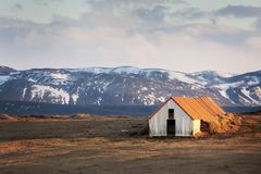 Shed for cattle on Iceland. With mountain and snow in background Stock Photo