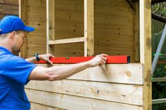 Worker check the level of wooden plank wall Stock Images