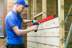 Shed construction - worker installing wooden facade planks Royalty Free Stock Image