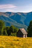 Shed on a grassy slope in mountains Royalty Free Stock Images
