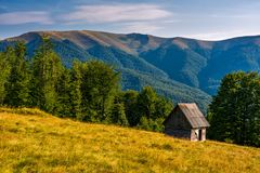 Shed on a grassy slope in mountains Stock Images