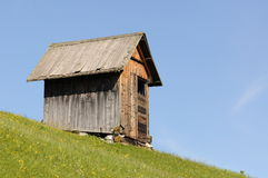 Shed on hillside. Side view of wooden shed on steep grassy hillside with blue sky background stock images