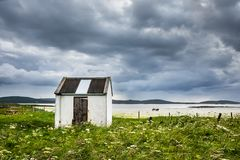 Shed house in the machair field next to the sandy beach, under the dark stormy sky royalty free stock photos