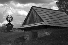 Shed with an iron windmill black and white. Stone shed with a shingle roof surrounded by a grass. In the background there is an old iron windmill. Photo taken in Stock Photography