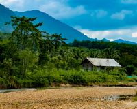 A shed in jungle. An old shed in middle of Jungle next to a river with mountains in background Royalty Free Stock Image