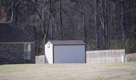 Shed Outhouse behind a home. A shed or outhouse provides homeowners with extra storage space for household items or lawn equipment Stock Photos