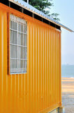 Shed by seaside. Yellow shed at sea beach, with blue sea view in perspective, shown as seaside view and color composition Stock Photos
