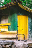 A shed or shack made of corrugated iron painted green and yellow Royalty Free Stock Photography