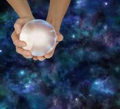 Shed some light on your future with a Crystal Ball Reading. Female hands holding a large scrying ball against a deep space background with plenty of copy space Stock Image