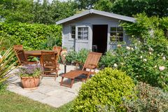 Shed with terrace and garden furniture. Gray shed with terrace and wooden garden furniture stock photography