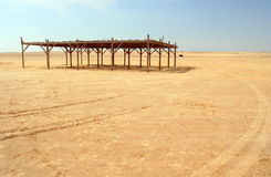 Shed in a tunisian desert. Visible tracks of quadricycles in the foreground Royalty Free Stock Image