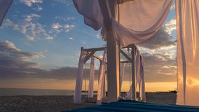 Sheds awning with fabric curtains on the beach in the evening. Sheds awning with fabric white curtains on the beach in the evening royalty free stock photography