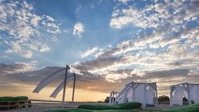Sheds awning with fabric white curtains on the beach. In the evening stock photography