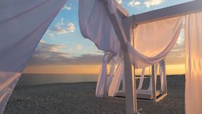 Sheds awning with fabric white curtains on the seashore breeze in the wind. Sheds awning with fabric white curtains on the beach in the evening royalty free stock photo