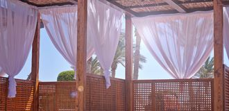 Sheds awning with fabric white curtains on the seashore breeze in the wind royalty free stock photos