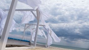 Flying in the wind fabric from the beach canopies on the beach. Sheds awning with fabric white curtains on the seashore breeze in the wind royalty free stock photography
