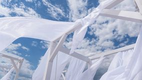 Flying in the wind fabric from the beach canopies on the beach. Sheds awning with fabric white curtains on the seashore breeze in the wind royalty free stock image