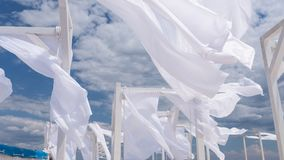 Sheds awning with fabric white curtains on the seashore breeze. In the wind royalty free stock image