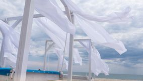 Sheds awning with fabric white curtains on the seashore in the wind. Sheds awning with fabric white curtains on the seashore breeze in the wind stock images