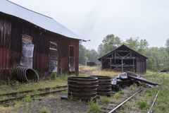 Sheds on railroad tracks. Dilapidated sheds along railroad tracks with rusting train wheels in countryside Stock Photo