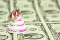 Sheel of money with a wedding cake and rings Stock Images