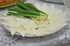 Sheep cheese curd and green onions placed on a plate. Green onions from the garden grandmother and fresh cheese from sheep Stock Photo