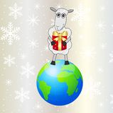 Sheep with a gift stands on a planet Earth Royalty Free Stock Images