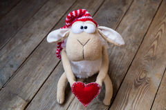 Sheep with heart. On wooden background Royalty Free Stock Photography