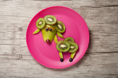 Sheep made of fresh fruits. On pink plate royalty free stock photography