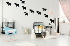 Sheep stickers in cozy bedroom. Blue rocking chair and stool in cozy bedroom interior with pastel lamp above bed and black sheep stickers on the wall Stock Photo