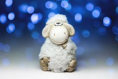 Sheep the symbol 2015 year. White sheep toy the Chinese symbol of 2015 year on blurred lights background royalty free stock image