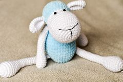 Sheep toy at bed. Near a stack of Soft blankets stock photos