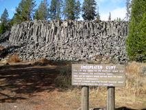 Sheepeater Cliffs with explanatory sign. Yellowstone National Park, USA - October 5, 2008: Columnar basalt at Sheepeater Cliff with explanatory sign in Royalty Free Stock Image