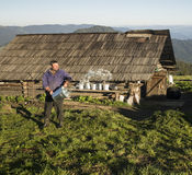 Sheepfold worker in Bucovina. A sheepfold worker in the Carpathian mountains, Bucovina region, starting his work early morning, right after sunrise Royalty Free Stock Image