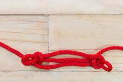 Sheepshank knot made with red rope on wooden background Stock Images